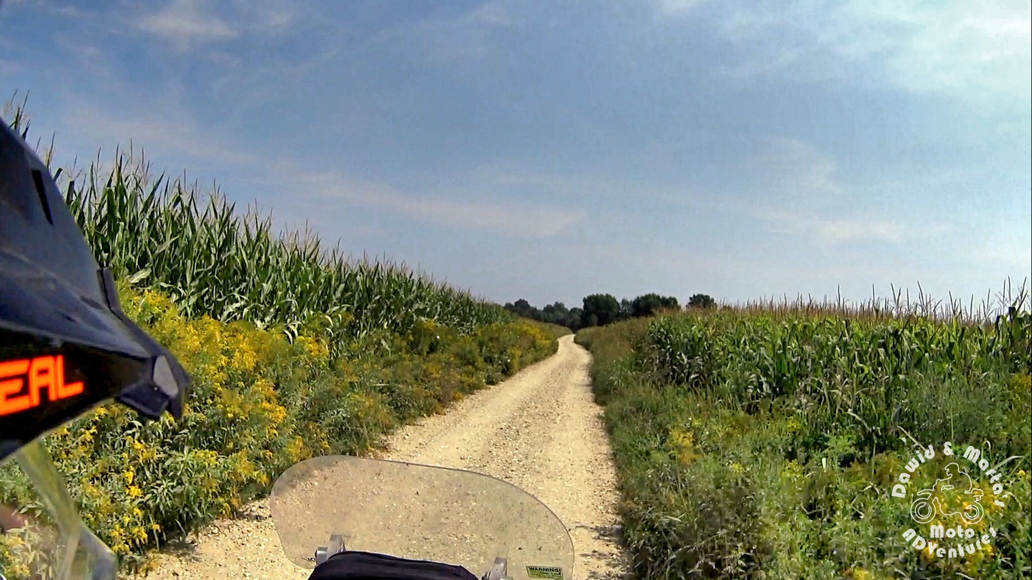 Leaving camping at the Drava River and riding offroad through the gravel road leading by the corn fields
